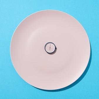 Witte plaat met whatch toont zes uur op een blauwe muur, kopie ruimte. plat leggen. concept van het beperken van de inname van voedseldieet en gewichtsverlies.