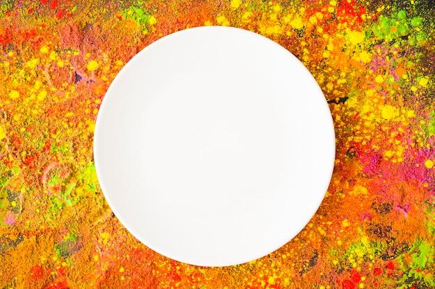 Witte plaat op kleurrijke tafel