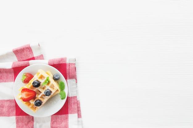 Witte plaat op rode theedoek met stapel zelfgemaakte belgische wafels