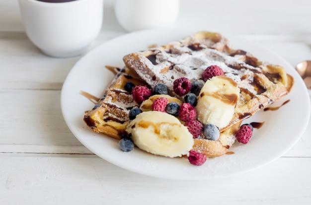 Witte plaat van belgische wafels met suikerpoeder, bevroren bessen, banaan en karamelsaus