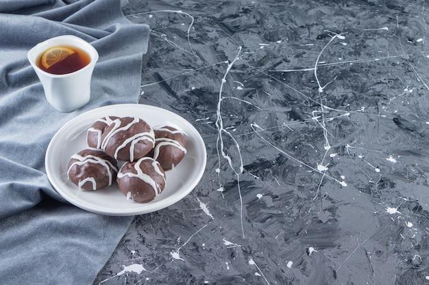 Witte plaat van chocoladeballen met kopje thee op marmeren tafel.