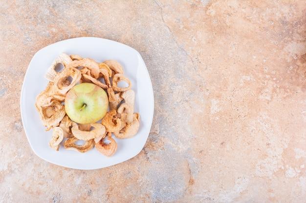 Witte plaat van droge appelringen en verse groene appel op marmeren tafel. hoge kwaliteit foto