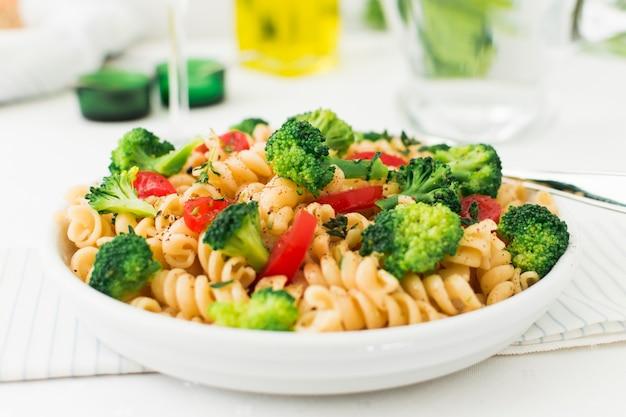 Witte plaat van fusilli pasta salade op servet