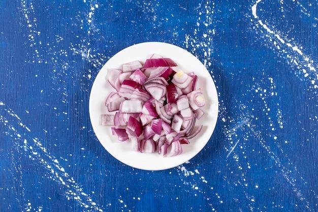 Witte plaat van gesneden paarse uien op marmeren oppervlak