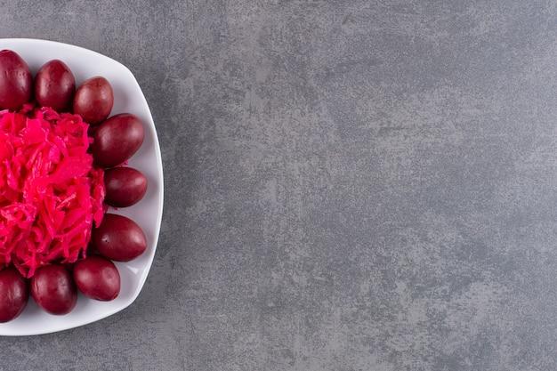 Witte plaat van ingemaakte pruimen en kool op stenen tafel.