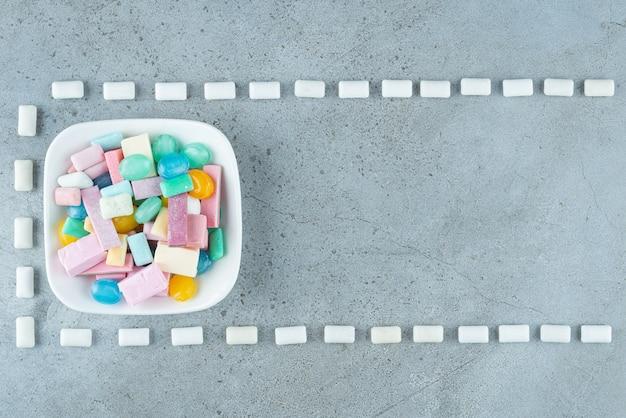 Witte plaat van kleurrijke kauwgom op stenen oppervlak.
