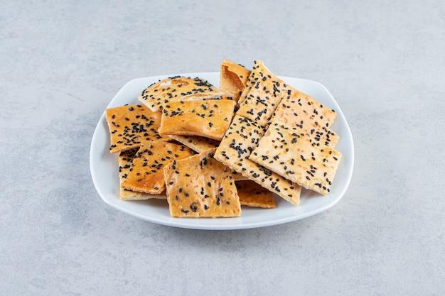 Witte plaat van knapperige crackers met zwarte zaden op marmeren achtergrond.