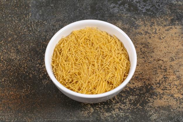 Witte plaat van rauwe droge spaghetti op marmeren oppervlak.