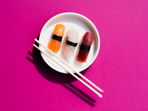 Witte plaat van sushi met karbonadestokken op een roze achtergrond
