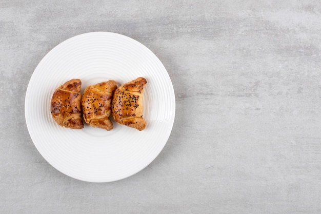 Witte plaat van vers lekker gebak op stenen tafel.