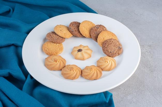 Witte plaat van verschillende zoete koekjes op stenen tafel.