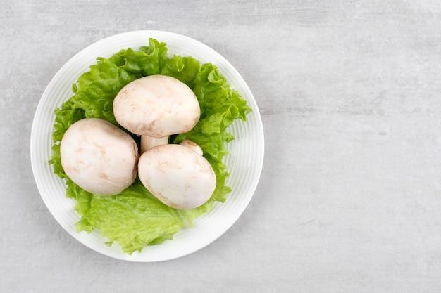 Witte plaat van verse witte champignons en sla op stenen tafel.
