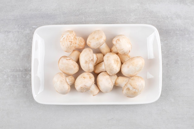 Witte plaat van verse witte champignons op stenen tafel.