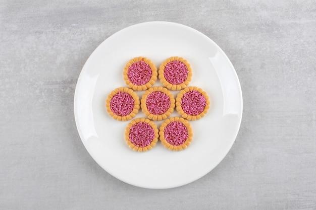 Witte plaat van zoete koekjes met roze hagelslag op steen.