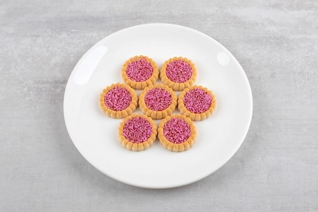 Witte plaat van zoete koekjes met roze hagelslag op stenen tafel.
