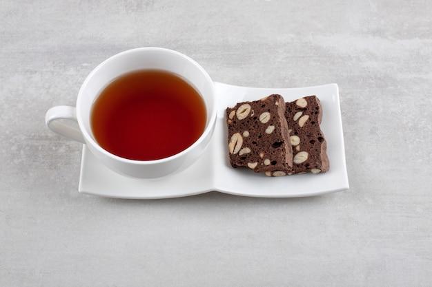 Witte plaat vol met sneetjes bruin brood met noten op een stenen tafel.