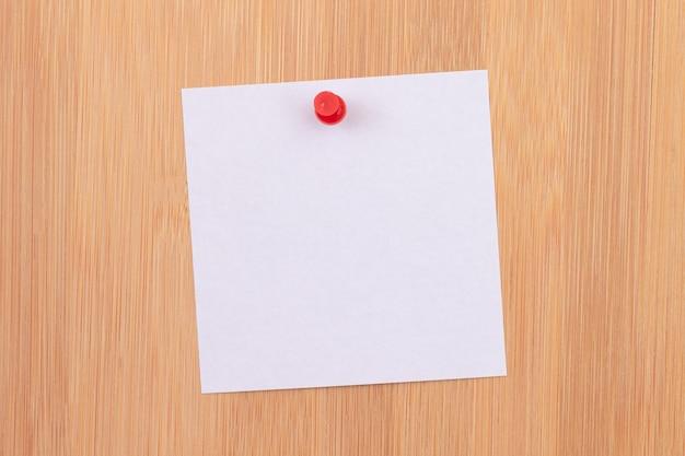 Witte plaknotitie vastgemaakt aan het houten prikbord