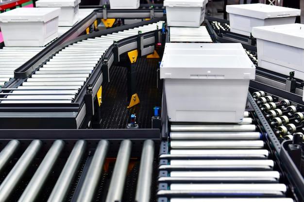 Witte plastic doos op transportband pakketten transportsysteem concept