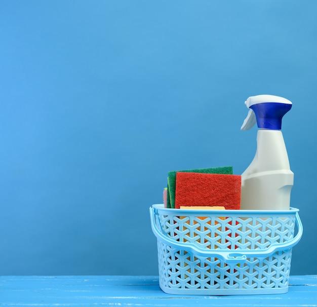 Witte plastic fles met mondstuk voor spray en schuim met afwasmiddel in plastic mand op blauwe achtergrond