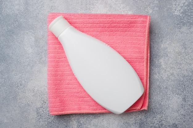 Witte plastic fles op een roze handdoek, badkameraccessoires,