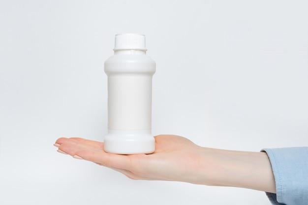Witte plastic geneeskundefles in een vrouwelijke hand.