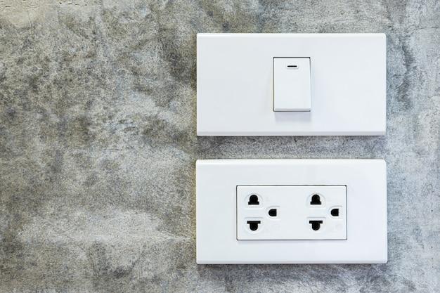 Witte plastic lichtschakelaar ingeschakeld en witte stopcontacten op betonnen muur, loft interieur stijl kamer.