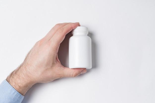 Witte plastic pil fles in mannenhand. medicijnpakket kunststof