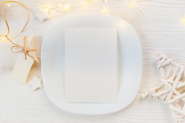 Witte plat met vel papier op hout