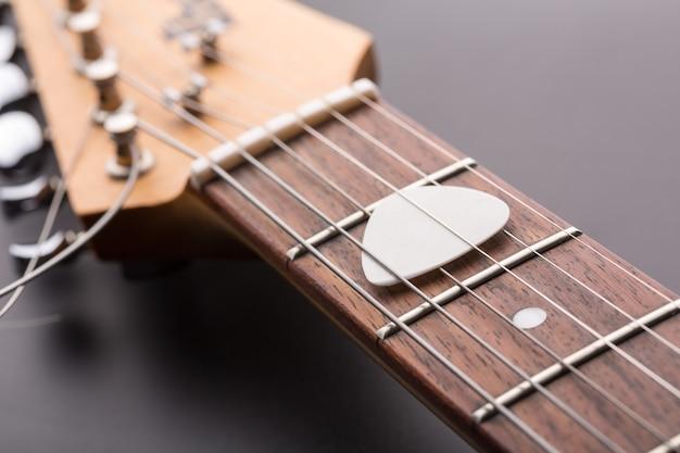 Witte plectrum in snaren voor elektrische gitaar