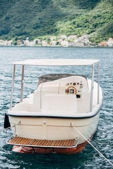 Witte plezierboot met luifel, achteraanzicht. afgemeerd in het water.