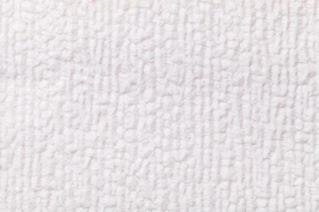 Witte pluizige achtergrond van zachte, wollige doek. textuur van textielclose-up.