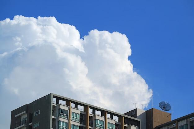 Witte pluizige gezwollen cumuluswolken op levendige blauwe hemel over de hoge gebouwen in bangkok, thailand