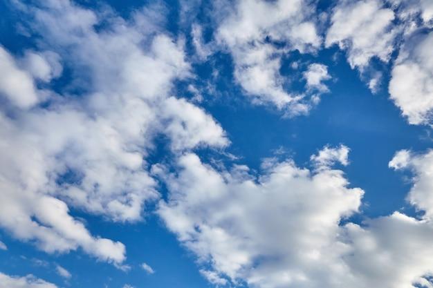 Witte pluizige stijgende wolken op een blauwe hemel