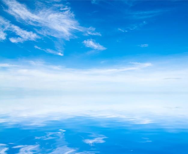 Witte pluizige wolken met regenboog in de blauwe lucht