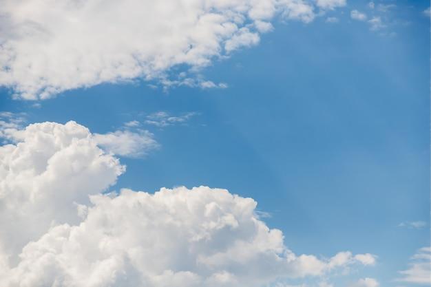 Witte pluizige wolken, mooie hemelachtergrond met zonnestralen