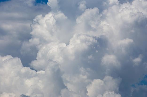 Witte pluizige wolken op de blauwe hemelachtergrond