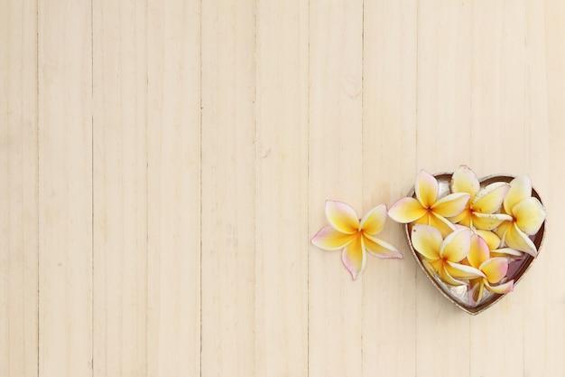 Witte plumeria-bloemen op hout