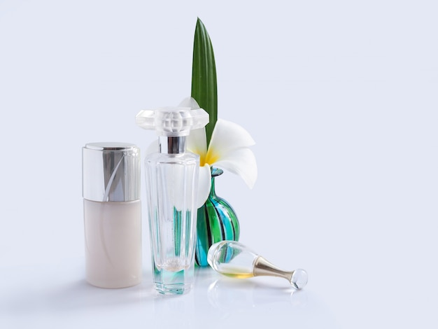 Witte plumeria spa-bloem in groene glazen vaas met transparante parfumflesjes en lotionfles.
