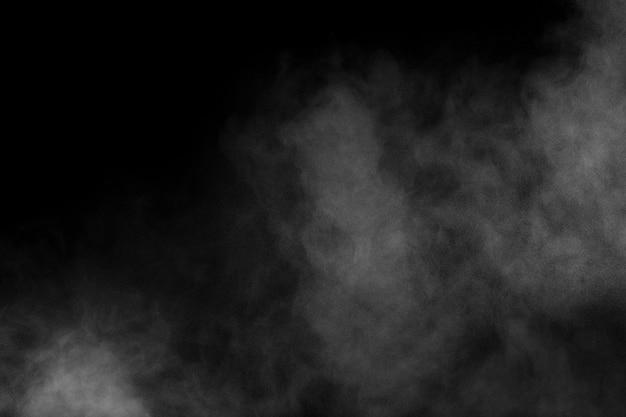Witte poeder explosie wolk tegen zwarte achtergrond. witte stofdeeltjes spatten.