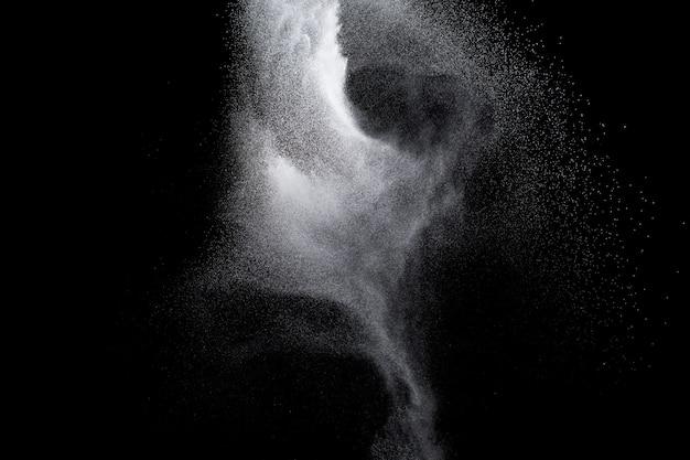 Witte poederexplosie die op zwarte achtergrond wordt geïsoleerd.