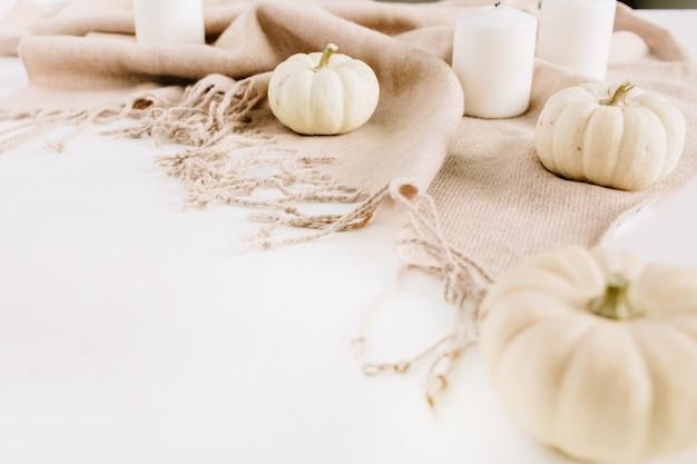 Witte pompoenen en kaarsen op beige plaid