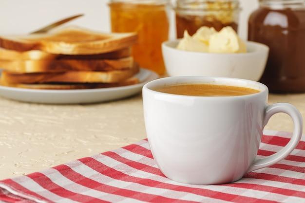 Witte porseleinkop met verse koffie op keukentafel