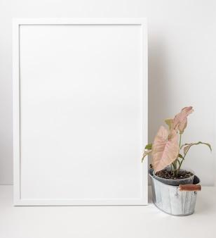 Witte portretframe mock-up decoratie met roze syngonium op gegalvaniseerd gepot op witte muurachtergrond, kopieer ruimte voor uw ontwerp
