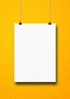 Witte poster opknoping op een gele muur met clips