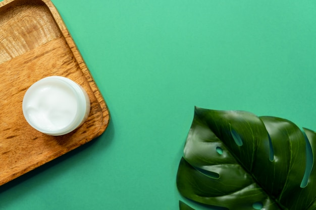 Witte pot gezichtscrème op een houten dienblad. groene achtergrond, bovenaanzicht, tropische bladeren. concept van natuurlijke cosmetica en spa.