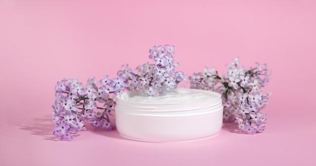 Witte pot hydraterende gezichtscrème met roze dop geïsoleerd op roze achtergrond met lila bloemen. eco cosmetologie of huidverzorging concept.