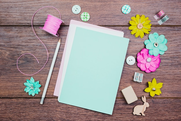 Witte potloden; toetsen; kleurrijke bloemen en roze spoel op houten tafel