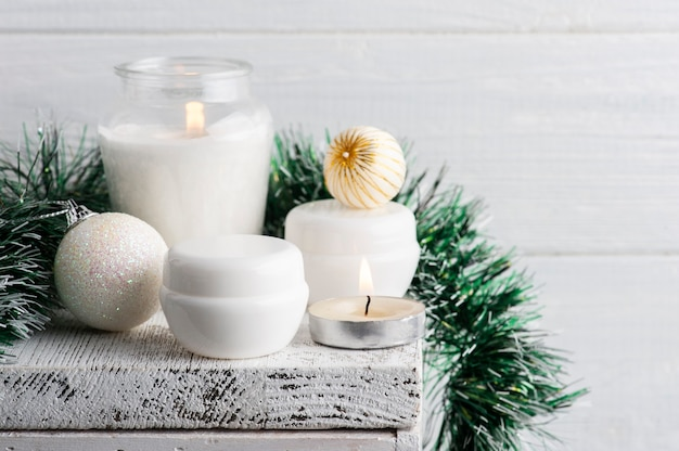 Witte potten in kerstmissamenstelling met aangestoken kaars
