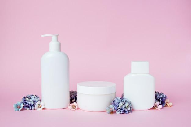 Witte potten met cosmetica met bloemen op roze