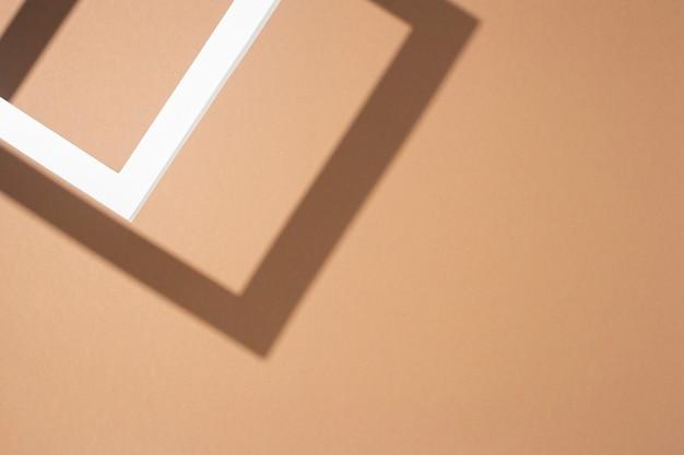 Witte presentatie podium frame op bruine achtergrond. bovenaanzicht, plat gelegd.